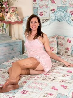 Lara Latex stripping in vintage nylons in her bed