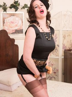 Karina Currie in vintage nylons spreading on a bed