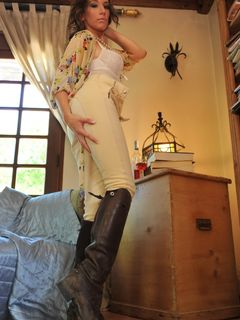 Curly Jemma Perry posing in her pants and boots