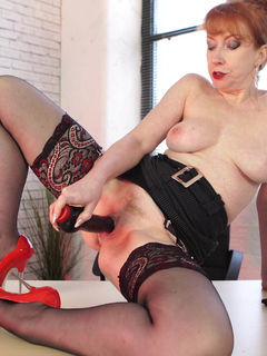 Curvy MILF Red XXX toys her cunt on the table